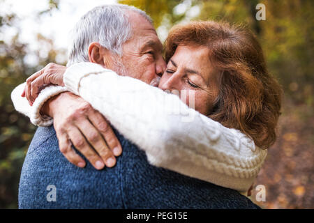 A close-up of a senior couple hugging in an autumn nature, kissing. - Stock Photo