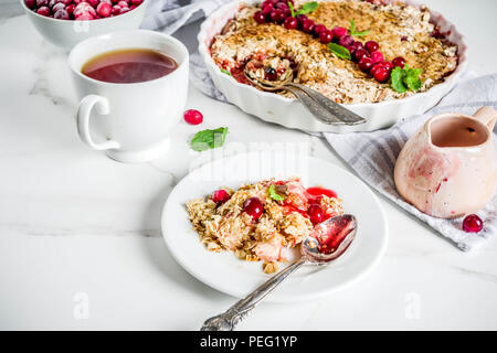 Traditional autumn winter pastries, homemade pie crumble with apples and cranberries, on a white marble table, copy space for text - Stock Photo