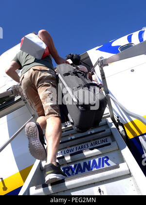 Rear view of Male Passenger climbs up the plane steps to board a Ryanair flight - Stock Photo