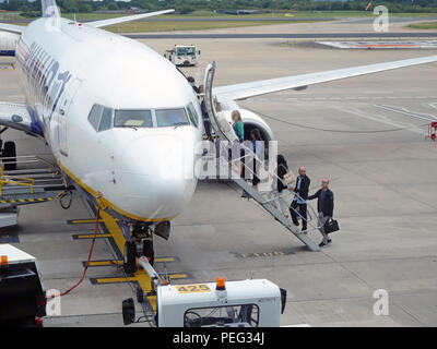 Passengers climbing steps up and onto their flight on the tarmac at Manchester International Airport, England - Stock Photo