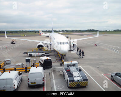 Showing all the plane from the front as passengers climb steps up and onto their flight on the tarmac at Manchester International Airport, England - Stock Photo