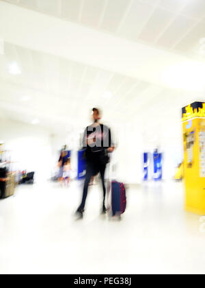 Tall male passenger moving fast through the arrivals area at Manchester International Airport - Stock Photo