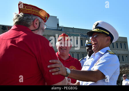 The superintendent of the Coast Guard Academy, Rear Adm. James Rendon, shares a laugh with veterans before the start of an event celebrating the city of New London becoming a 'Coast Guard City,' New London, Conn., Aug. 14, 2015. Speakers at the event included Vice Adm. Sandra Stosz, deputy commandant for mission support at the Coast Guard, Sen. Richard Blumenthal of Connecticut, and New London Mayor Daryl Justin Finizio. New London is home to the Coast Guard Academy, Coast Guard Station New London, U.S. Coast Guard Research and Development Center, the Marine Safety Lab, the International Ice P - Stock Photo