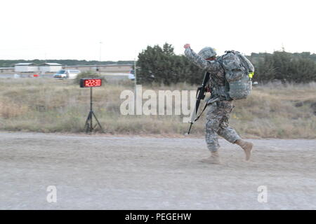 "Spc. Fotu Malaefono, a Patriot launching station enhanced operator/maintainer with Rear Detachment, 4th Battalion, 5th Air Defense Artillery Regiment, 69th ADA Brigade, throws his fist into the air as he completes a ruck march Aug. 11, on Fort Hood, Texas, during Lightning Warrior Week. Malaefono, a Jackson, Mich., native, won the title of ""Soldier of the Quarter"" for the brigade. (U.S. Army Photo by Staff Sgt. Kimberly Lessmeister/69th ADA Bde. Public Affairs Office) - Stock Photo"