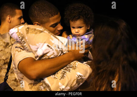 Sgt. Emmanuel Torres holds one-year-old Noah, following a deployment to the United States Pacific Command at Marine Corps Air Station Cherry Point, North Carolina, Aug. 9, 2015. Marine Tactical Electronic Warfare Squadron 2 returned from a deployment in support of the United States Pacific Command. The Squadron provided airborne electronic warfare in the Asia-Pacific region during this deployment. Torres is an advanced aircraft communications navigation technician Marine Aviation Logistics Squadron 14. (U.S. Marine Corps photo by Cpl. N.W. Huertas/Released) - Stock Photo