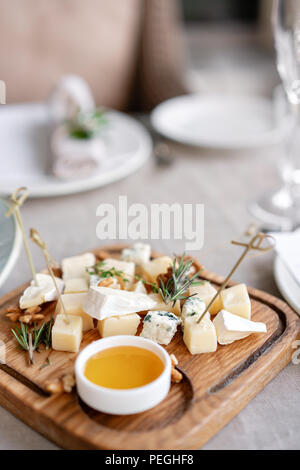 Cheese plate. Delicious cheese mix with walnuts, honey on wooden table. Tasting dish on a wooden plate. Food for wine. - Stock Photo