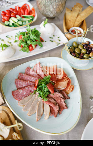 Food tray with delicious salami, pieces of sliced ham, sausage. Cutting sausage and cured meat on a celebratory table. - Stock Photo