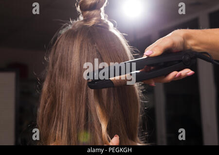hairdresser curling a hair strand of a girl - Stock Photo