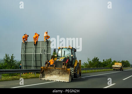 BELGRADE, SERBIA - MAY 15, 2017: Three men in orange work suits put up new traffic board sign on a newly reconstructed major road near Serbian capital city of Belgrade in a hazy day - Stock Photo