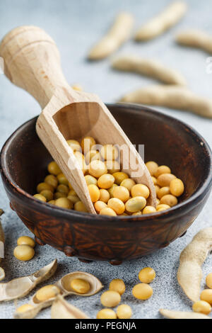 Soybeans in a clay bowl and pods on a gray concrete surface. Selective focus - Stock Photo