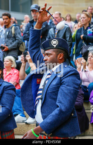 Glasgow, UK. 15th Aug 2018. Street performances continue in Buchanan Street, Glasgow with more international pipe bands playing near the Donald Dewar statue to entertain the public for free. The Pipe Band championships conclude on Saturday 18th August at Glasgow Green. Pictue of OWEN RUSSELL from USA playing with the Simon Frase University Pipe Band from British Columbia, Canada Credit: Findlay/Alamy Live News - Stock Photo