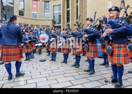 Glasgow, UK. 15th Aug 2018. Street performances continue in Buchanan Street, Glasgow with more international pipe bands playing near the Donald Dewar statue to entertain the public for free. The Pipe Band championships conclude on Saturday 18th August at Glasgow Green, Members of the Simon Fraser University Pipe Band from British Columbia, Canada Credit: Findlay/Alamy Live News - Stock Photo