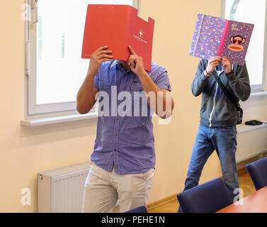 16 August 2018, Germany, Leipzig: Two defendants accused of a particularly serious breach of the peace enter a courtroom in the district court before the trial begins. More than two and a half years after the riots of neo-Nazis in Leipzig's Connewitz district, the first defendants face their trial. During the riots on 11 January 2016, the windows of numerous shops were smashed and cars set on fire. Connewitz is considered a stronghold for leftist and autonomous groups. Credit: dpa picture alliance/Alamy Live News - Stock Photo