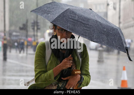 Trafalgar Square. London. 16 Aug 2018 - Tourists shelter from the rain beneath umbrellas during heavy downpour in the capital.  Credit: Dinendra Haria/Alamy Live News - Stock Photo