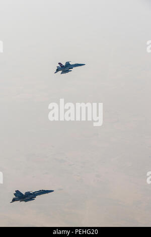 U.S. Marine Corps F/A-18s with Marine Fighter Attack Squadron 232 link up and perform an Air to Air refuel with a Royal Canadian Air Force CC-150 Polaris air-to-air refueller during a combat mission in the skies of Iraq on July 19, 2015. The 'Red Devils' of VMFA-232 are currently deployed with the Special Purpose Marine Air Ground Task Force-Crisis Response-Central Command and provide offensive strike and close air support to Operation Inherent Resolve and the global fight against the Islamic State of Syria and the Levant. (Courtesy Photo by Op IMPACT) - Stock Photo