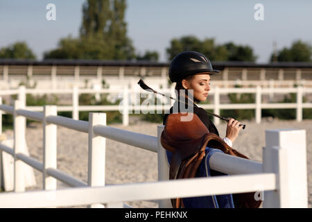 elegant rider woman in helmet with whip - Stock Photo