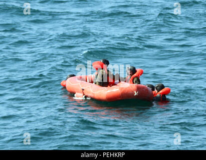 Air crew members from the1st Battalion, 137th Aviation Regiment, 185th Theater Aviation Brigade climb onto a life raft in the North Arabian Gulf, Aug. 24, 2015. The crew members were participants in an all-day training event that was part of an effort to refine and develop new tactics, techniques and procedures for deploying a life raft in the event a U.S. Army aircraft was to go down in the North Arabian Gulf. (U.S. Army National Guard photo by Capt. Allen Baxter/Released) - Stock Photo