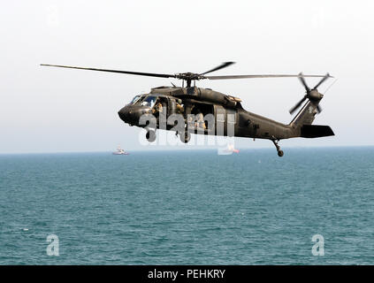 A UH-60 Black Hawk from the 1st Battalion, 137th Aviation Regiment, 185th Theater Aviation Brigade flies over the North Arabian Gulf, Aug. 24, 2015. The aircraft was participating in an all-day training event that allowed crew members from across the 185th Theater Aviation Brigade to develop new tactics, techniques and procedures for the rescue and recovery of personnel in the event of a downed aircraft in the North Arabian Gulf. (U.S. Army National Guard photo by Capt. Allen Baxter/Released) - Stock Photo