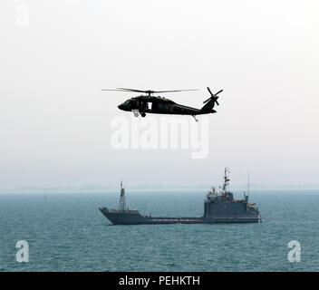 A UH-60 Black Hawk from the 1st Battalion, 137th Aviation Regiment, 185th Theater Aviation Brigade flies over the USAV Corinth in the North Arabian Gulf, Aug. 24, 2015. The aircraft was participating in an all-day training event that allowed crew members from across the 185th Theater Aviation Brigade to develop new tactics, techniques and procedures for the rescue and recovery of personnel in the event of a downed aircraft in the North Arabian Gulf. (U.S. Army National Guard photo by Capt. Allen Baxter/Released) - Stock Photo