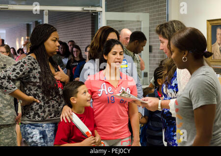 As the first day of school commences, families and their children swarm the entranceway of Clarke Elementary School, Fort Hood, Texas, getting directions to the appropriate classrooms, Aug. 24, 2015. The school staff members were eager to help families get checked in as smoothly as possible to make the transition of dropping the children off easier. (U.S. Army photo by Staff Sgt. Michael Folkerth) - Stock Photo