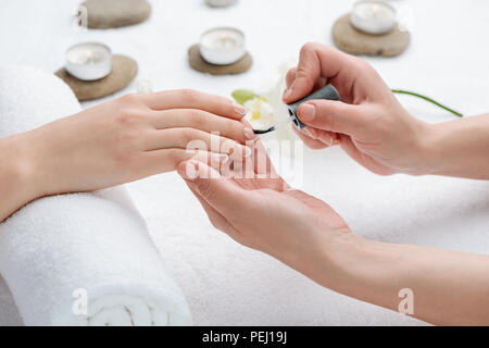 Doing a French manicure in a salon. Simple, chic and polished look for nails. SPA and beauty treatment procedures. - Stock Photo