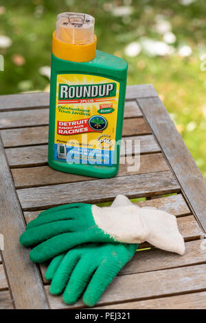 Paris, France - August 15, 2018 : Herbicide on a wooden table in a french garden. Roundup is a brand-name of an herbicide containing glyphosate, made  - Stock Photo