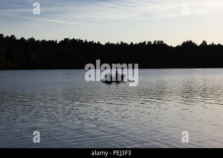 Family in a boat at sunset on the calm waters of a lake and behind a forest enjoying life - Stock Photo