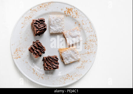 Delicious Chocolate Brownies and Alfajores. On a white background. - Stock Photo
