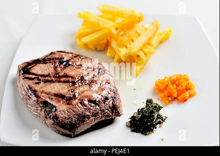 dish with grilled meat. Meat, French fries accompanied by chimichurri sauce - Stock Photo