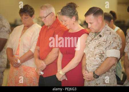 U.S. Marine Corps Sgt. Maj. Christopher J. Garza (right), outgoing Sergeant Major, Advanced Infantry Training Battalion (AITB), School of Infantry-East (SOI-E), and his family bow their heads for the prayer during the AITB Post and Relief aboard Camp Geiger, N.C., Aug. 4, 2015. Staff of SOI-E and family members attended the AITB Post and Relief Ceremony where Sgt. Maj. Garza relinquished his post to Sgt. Maj. Baiotto. (U.S. Marine Corps by SSgt Mark E. Morrow Jr, Combat Camera, SOI-E/ Released) - Stock Photo