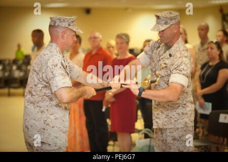 U.S. Marine Corps Lt. Col. Theodore C. Bethea II (left), Commanding Officer, Advanced Infantry Training Battalion (AITB), School of Infantry-East (SOI-E), hands the Non-Commissioned Officer Sword to Sgt. Maj. Bradley W. Baiotto (right), oncoming Sergeant Major, AITB, SOI-E, during the AITB Post and Relief aboard Camp Geiger, N.C., Aug. 4, 2015. Staff of SOI-E and family members attended the AITB Post and Relief Ceremony where Sgt. Maj. Garza relinquished his post to Sgt. Maj. Baiotto. (U.S. Marine Corps by SSgt Mark E. Morrow Jr., Combat Camera, SOI-E/ Released) - Stock Photo