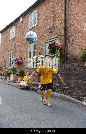 Boys in Wolverhampton Wanderers FC replica kits playing football outside the birthplace of Wolves and England footballing legend Billy Wright in Ironb - Stock Photo