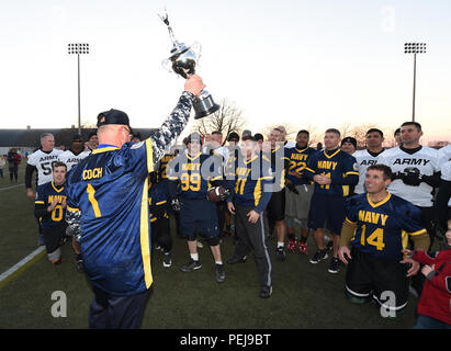 151204-N-PX557-283 NEWPORT, R.I. (Dec. 4, 2015) Jim Morris, coach of the U.S. Naval War College (NWC) Navy flag football team, holds the winner's trophy following an Army-Navy flag football game at Nimitz Field onboard Naval Station Newport in Newport, Rhode Island. The game was held as a precursor to the college football rivalry game between U.S. Naval Academy, Navy Midshipmen, and U.S. Military Academy, Army Black Knights, scheduled for Dec. 12, at Lincoln Financial Field in Philadelphia, Pa. The NWC Navy flag football team triumphed over the NWC Army team with a final score of 26-0. (U.S. N - Stock Photo