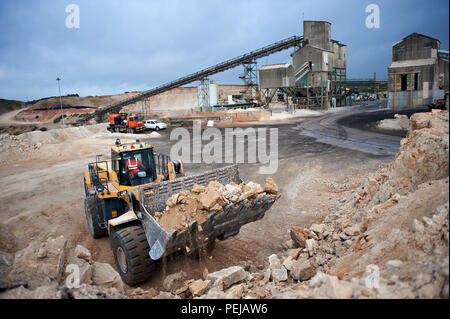 Excavating and picking up mined aggregate from the quarry floor, in a powerful komatsu excavator, at Whitwell quarry, Whitwell, Derbyshire UK. - Stock Photo