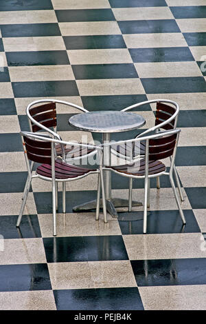 A Vacant Chrome Table And Four Chairs Sit Unused On A Checkerboard