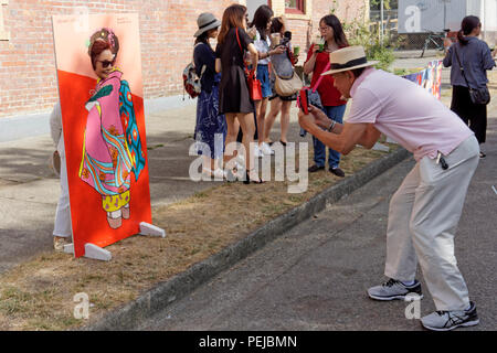 Man photographing his wife posing in a head in the hole cutout at the 2018 Powell Street Festival in Japantown, Vancouver, BC, Canada - Stock Photo
