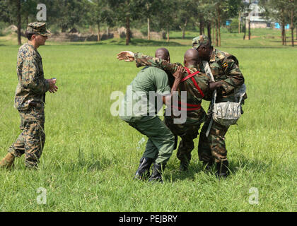 Petty Officer 2nd Class Robert Otte (left), corpsman and chief instructor with Special-Purpose Marine Air-Ground Task Force Crisis Response-Africa, evaluates Uganda People's Defense Force medics as they carry and injured soldier to a safe zone during a tactical combat casualty care exercise at Camp Singo, Uganda, Dec. 8, 2015. The UPDF medics and corpsmen are training together to improve tactical medical care skills while strengthening the bond between the partner nations. (U.S. Marine Corps photo by Cpl. Olivia McDonald/Released) - Stock Photo