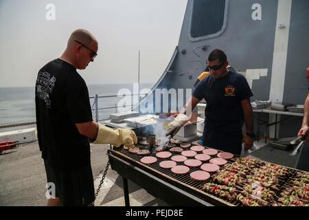 GULF OF ADEN (Aug. 29, 2015) U.S. Marine Master Sgt. Brian Stirrat, left, cooks on the grill during a steel beach picnic aboard the amphibious transport dock ship USS Anchorage (LPD 23). Stirrat is the Operations Chief with Delta Company, Light Armored Reconnaissance Detachment, Battalion Landing Team 3rd Battalion, 1st Marine Regiment, 15th Marine Expeditionary Unit. Elements of the 15th MEU are embarked aboard the Anchorage, which is part of the Essex Amphibious Ready Group, and is deployed in support of maritime security operations and theater security cooperation efforts in the U.S. 5th Fl - Stock Photo