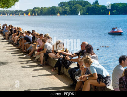Hanover, Lower Saxony, July 5, 2018: Guests at the Maschsee Festival rest on the east bank wall and enjoy their lunch break in the sun. - Stock Photo