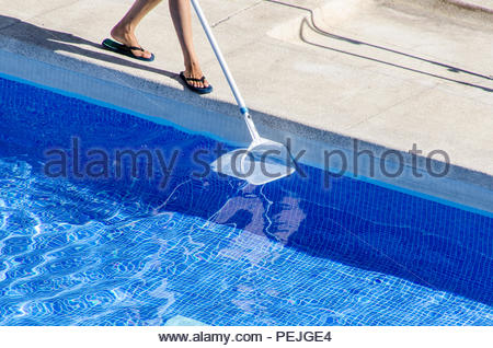 man in flip flop cleaning the swimming pool side with a net - Stock Photo