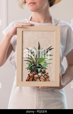Young blonde woman in a long beige apron is standing in a small workshop and holding in hands mosaic picture in a frame. - Stock Photo