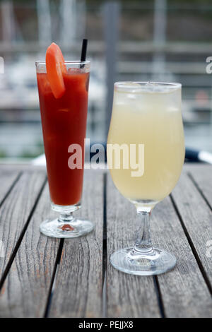 Two drinks, a Bloody Mary and an iced ginger beer, outdoors on a wooden table - Stock Photo