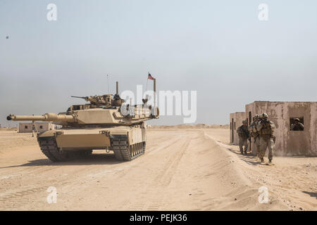 KUWAIT (Aug. 28, 2015) U.S. Marines with Kilo Company, Battalion Landing Team 3rd Battalion, 1st Marine Regiment, 15th Marine Expeditionary Unit, rehearse urban patrolling techniques as an M1A1 Abrams tank provides security during military operations in urban terrain training. During the training Marines rehearsed patrolling through urban areas and immediate action drills. Elements of the 15th MEU are ashore in Kuwait for sustainment training to maintain and enhance the skills they developed during their pre-deployment training period.  The 15th MEU is embarked aboard the Essex Amphibious Read - Stock Photo