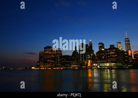 NEW YORK, NY - JULY 03: Financial District, Lower Manhattan skyline after sunset as seen from Brooklyn Bridge Park, Brooklyn - Stock Photo