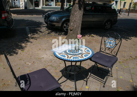 Round cafe table with colorful mosaic top and water filled jar with a pink rose top and two wrought iron chairs with cushions on the sidewalk near the - Stock Photo