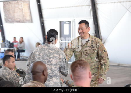 U.S. Army Maj. Gen. K.K. Chinn, Army South commander, gives a coin to a Soldier stationed at Soto Cano Air Base, Honduras, Dec. 8, 2015. Chinn came to Soto Cano to give the Soldiers a better idea of how their work is helping to build relationships between partner nations throughout the Central American area of responsibility. (U.S. Air Force photo by Senior Airman Westin Warburton/Released) - Stock Photo