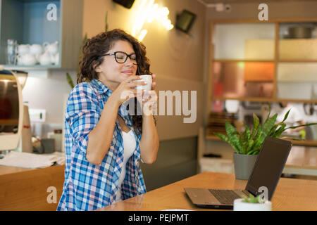 Beautiful young  womanwith curli hair enjoying a cup of coffee. - Stock Photo