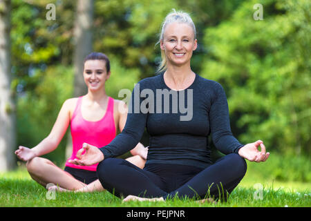 Mature fit healthy middle aged female yoga teacher yogi teaching young woman at yoga practice outside in a natural tranquil green environment - Stock Photo