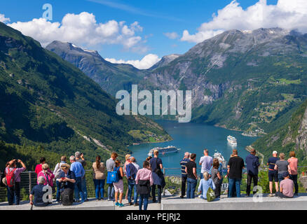 Geiranger, Norway. Tourists at the viewpoint overlooking the town of Geiranger and Geirangerfjord, Norway - Stock Photo