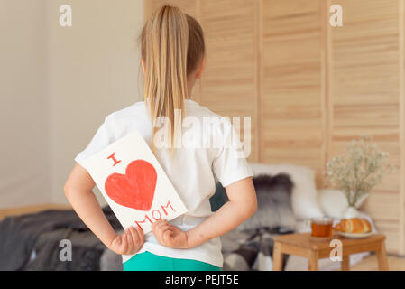 Little girl paints greeting card for Mom on Mother's Day with the inscription I love you mom . Indoors. Mother's Day concept. - Stock Photo
